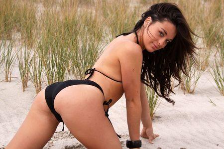 beach babe: giovane donna in bikini nero sulla spiaggia