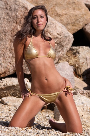 babe in gold string bikini in front of rocks on a beach photo