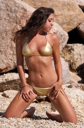 hot sexy girls: babe in gold string bikini in front of rocks on a beach Stock Photo