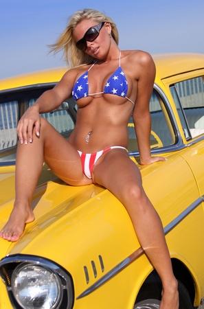 Patriottische Bikini Babe poseren voor klassieke American Hot Rod Stockfoto