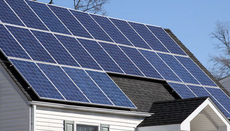 solar panel roof: sunlit solar panels covering the roof of a house Stock Photo
