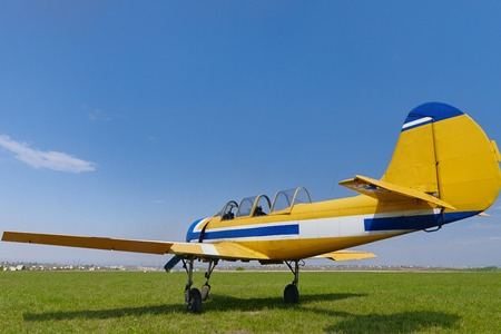 small plane: Yellow small plane on green grass against blue sky, two peole