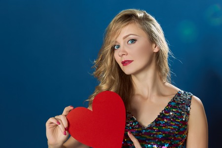 st  valentine: St Valentine day young blond woman holding red heart on blue