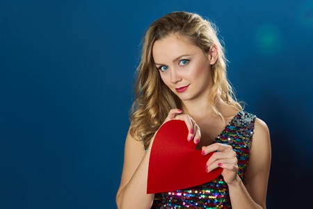 valentine s: Valentine s day blond girl breaking red heart on blue background Stock Photo