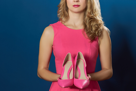 no heels: Blong oman holging high hill pink new shoes blue background