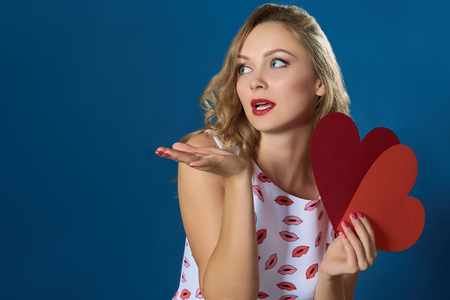air kiss: Blond woman holding two hearts kissing red lips air kiss blue background