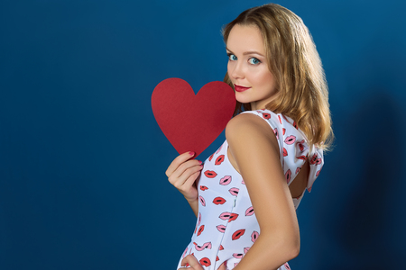 woman profile: Profile portrait of a pretty blond woman holding red paper heart on blue background