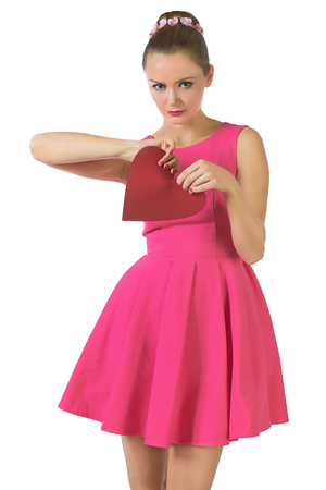 pink dress: Young pretty woman in pink dress breaking tearing red heart, end of relationships, Valentines isolated white Stock Photo