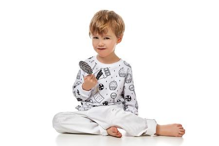 Blonde baby jongen in pijama met candys zwart en wit, izolated op een witte achtergrond