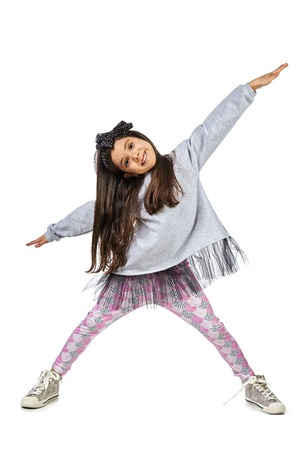 preadolescence: Girl in gray dress and pink tights posing with hands on hip. Full length studio shot isolated on white. Stock Photo