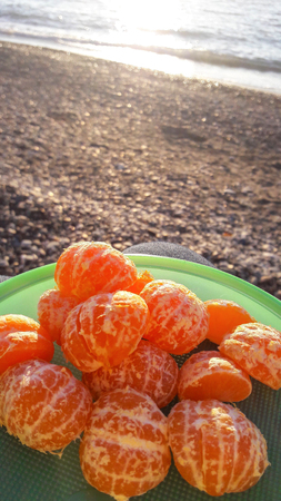Photo of the cleaned tangerines are lying on a plate, in the background is a stone beach and the sea