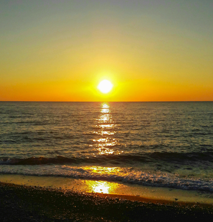 Sunset on the sea, with the reflection on the water of the solar track, small waves and a stone beach Stockfoto