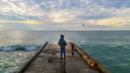 Photo of a child standing on the pier and looking into the sea, past the gulls fly by, on the sea a slight excitement