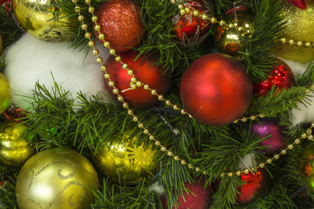 Christmas background with gold and red balls on the Christmas tree, with beads,
