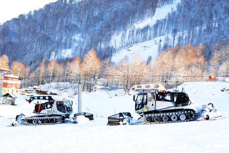 Machines for snow removal are moving along the mountain, clearing the road for skiers, against the background of the forest, mashiny of silver color