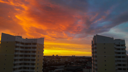 Beautiful golden sunset in the city against the backdrop of two high-rise buildings, flowing into the dark sky Stockfoto