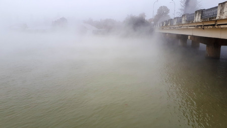 the edge of the bridge and the fog from the river, visible buildings through the fog, silhouettes of trees