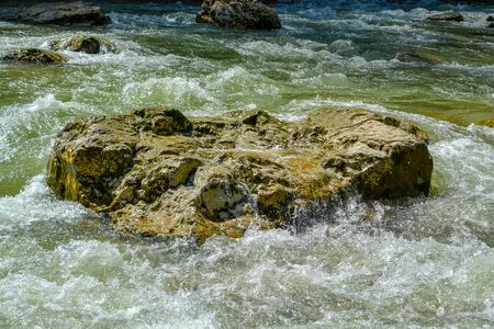 A cascade of water flowing in the river runs along the rocks, a beautiful landscape, rich colors.