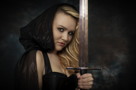 female hand: Blonde young woman in black cape with sword