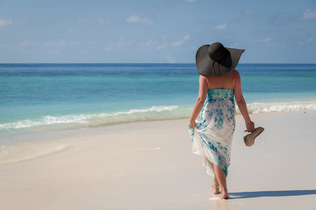 Maldives, young woman walking along the beach with sunhat and high heels on the hand