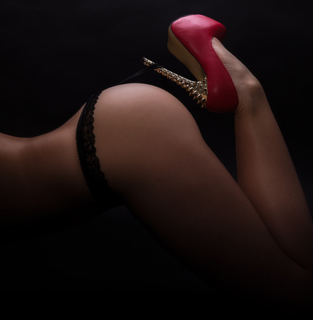 black sex: Bottom of a woman in black panty with a red highheel Stock Photo