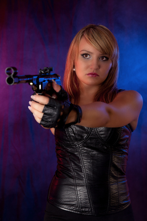 Young blond woman in leather and with a gun
