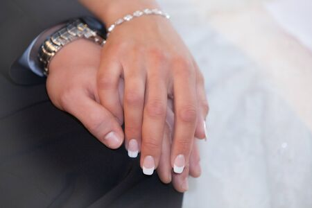 Bride and groom hold their hands romantically