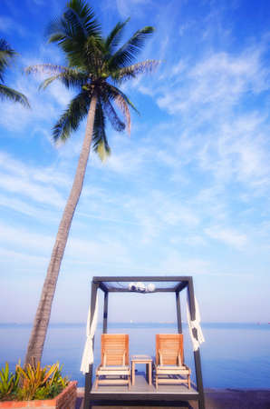 twain: twain wood bed pool at sea with palm Stock Photo