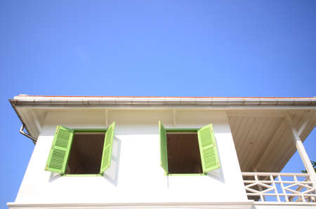 Wit huis met groene windown en blauwe hemel Stockfoto