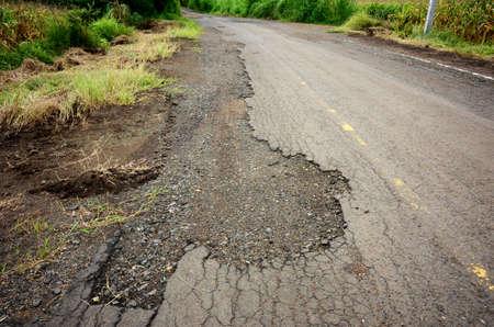 Asphalt road break and trees beside