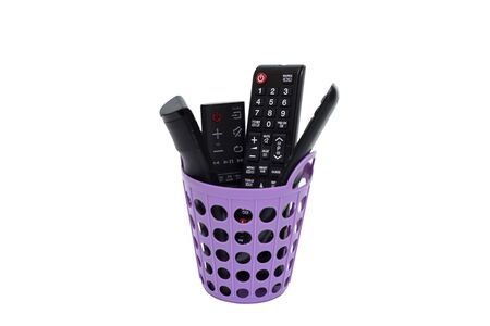 Smart remotes TV on purple basket and on white  with  . 版權商用圖片