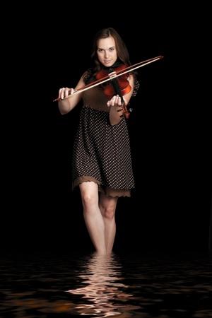 violinist isolated on black background photo