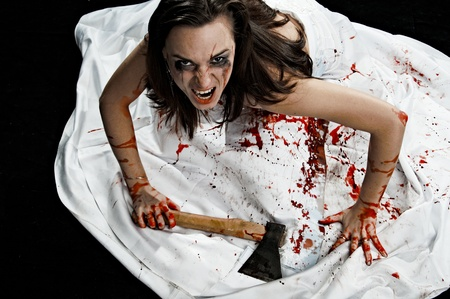 sectarian: yelling woman with axe in blood on black background Stock Photo