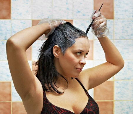 pretty beautiful young woman dyeing hairs photo