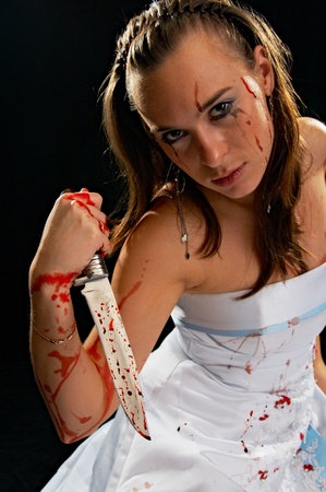 portrait of the sad woman with knife with blood on black background photo