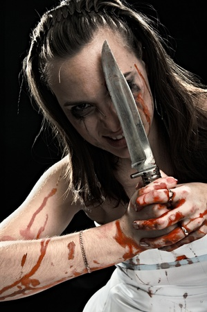 woman with knife isolated on black background photo