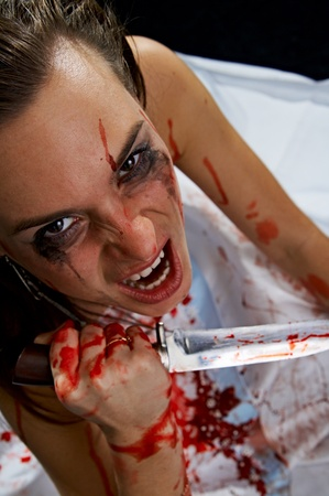 woman with knife in blood on black background photo