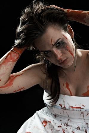 portrait tearful woman in blood on black background photo