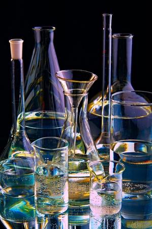 chemical flasks on black background photo