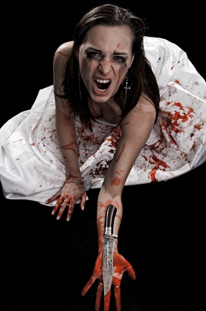 yelling woman with knife in blood on black background photo