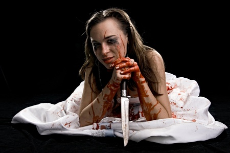 woman in blood with knife isolated on black background photo