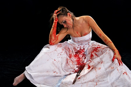 sad woman with knife isolated on black background