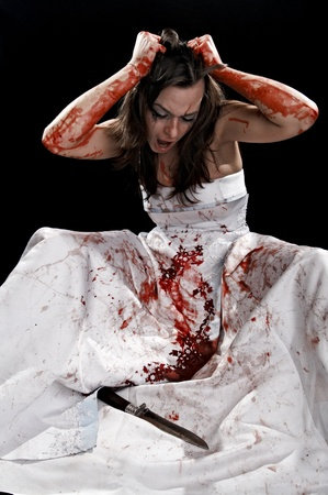 portrait of the mad woman with knife on black background photo