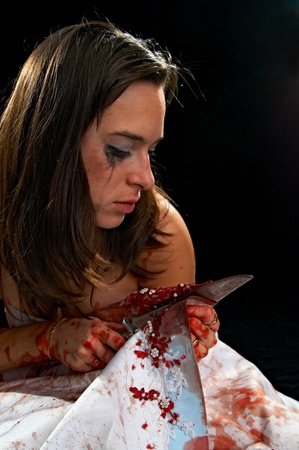 portrait of the brunette with knife in blood on black background photo
