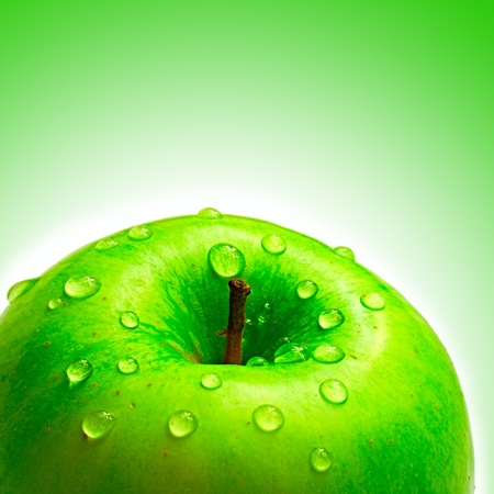 beautiful apple with droplet of water on green background photo