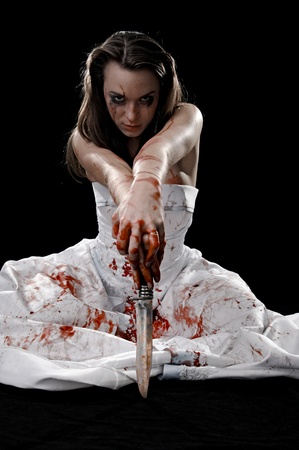 brunette with knife in blood isolated on black background photo
