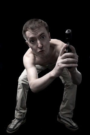 portrait of the funny person with weapon isolated on black background photo