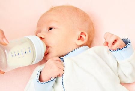 nursing bottle: nursing beautiful baby by milk from bottle Stock Photo