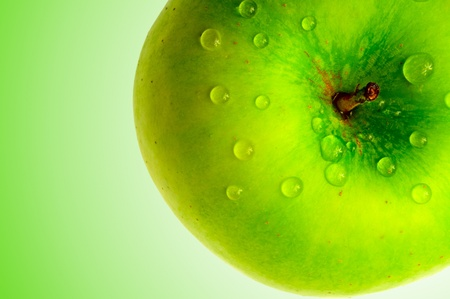green apple in dewdrop on green background photo