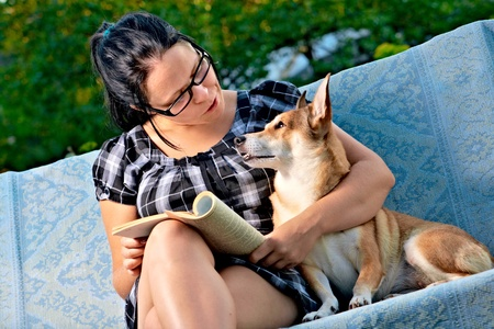 pretty young woman with dog reading magazine photo